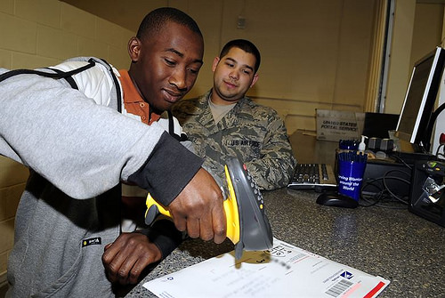 Jared Taylor, 16, scans a package under the guidance of Senior Airman Nolan Luna-Chavez at the RAF Mildenhall post office Aug. 3, 2012