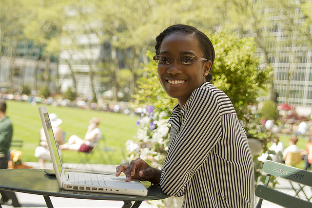 Black student working at laptop outside