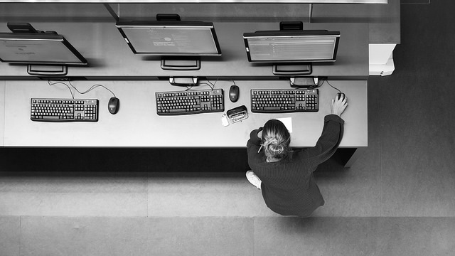 Overhead shot of a white woman doing research on a library computer