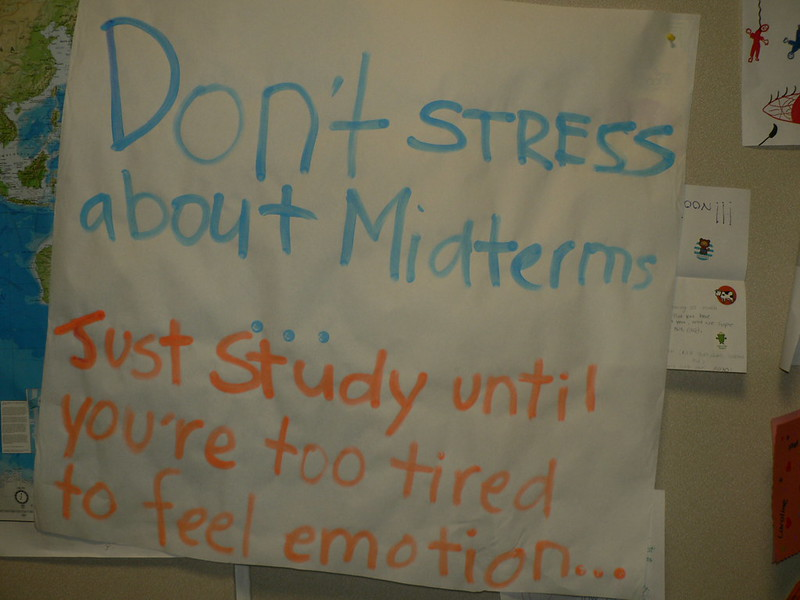 Large white poster on a bulletin board with the message: Don't stress about midterms...Just study until you're too tired to feel emotion...