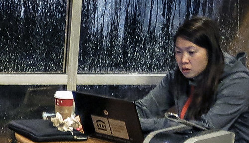 Asian woman working on laptop at Starbucks